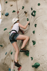 A teen girl climbing on a rock wall.