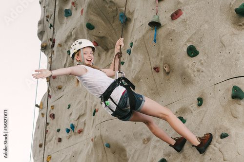 A teen girl climbing on a rock wall leaning back against the rop