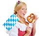 Woman with bavarian flag eating pretzel