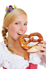 Woman in dirndl eating a pretzel