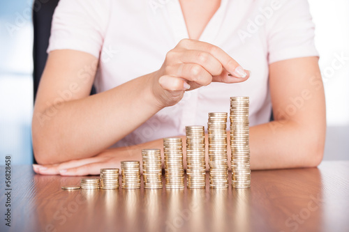Woman Hand Stacking Gold Coin