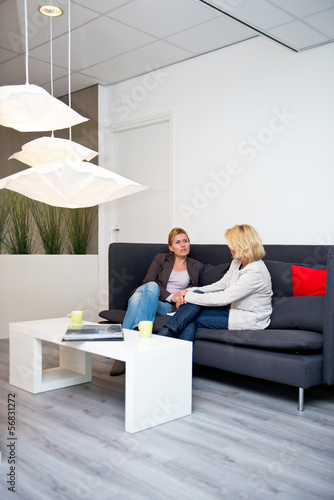 Two women in a corporate reception waiting area