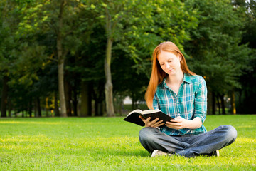 A young Christian woman reading a Bible outdoors
