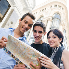 Three tourist looking to camera with a map