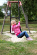 Happy toddler girl on a swing in city park