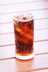 glass of cola with ice with wood background