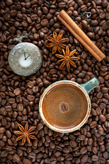 Coffee beans, cup of coffee, cinnamon and star anise