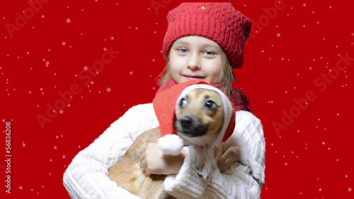 girl and dog in santa hat on a red background with falling snow
