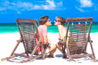 Couple on a tropical beach sitting in chairs and relaxing