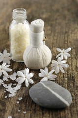 White spring flower, salt in glass ,stone on old wood