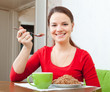 woman in red eats buckwheat