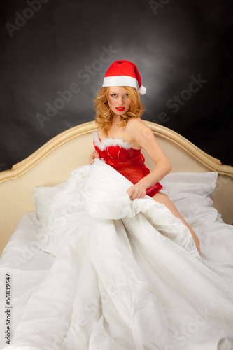 Blonde dressed as Santa Claus in bed on a gray background.