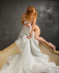 Blonde naked in bed on a gray background.