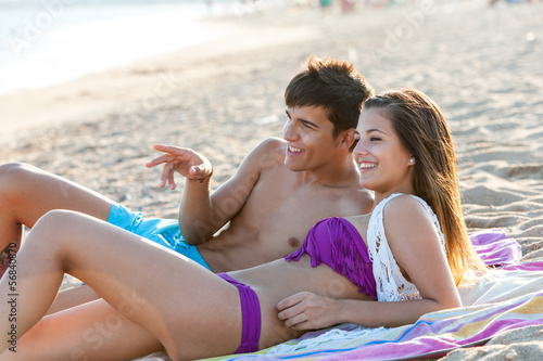 Teen couple enjoying afternoon on beach.