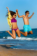 Teen couple in swim wear jumping.