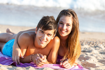 Teen couple together on beach.