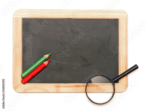 Colorful pencil with magnifying glass on blank blackboard