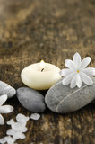 grey stones and white spring flower, candle on old wood