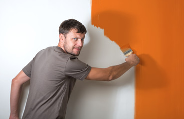 Bearded man paints the white wall
