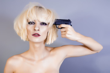 woman pointing the pistol on her head