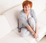Happy mature woman on sofa