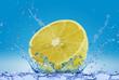 Cytryna wpadająca do wody na niebieskim tle