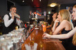 Handsome bartender making cocktails for beautiful women