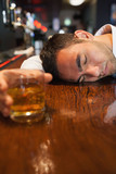 Unconscious businessman holding whiskey lying on a counter