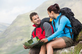 Couple resting after hiking uphill and holding map