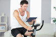 Smiling sporty man exercising on bike and using tablet