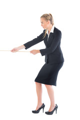 Focused blonde businesswoman pulling a rope