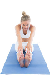 Toned focused blonde sitting on exercise mat stretching legs