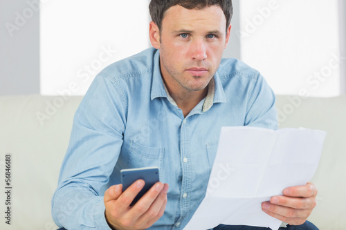 Serious casual man holding calculator and document