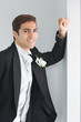 Cheerful young bridegroom leaning against wall