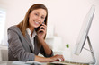 Saleswoman in office talking on mobile phone