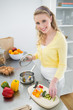 Smiling cute blonde putting vegetables in a pot