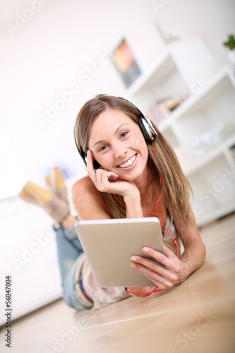 Smiling girl laying on the floor and listening to music