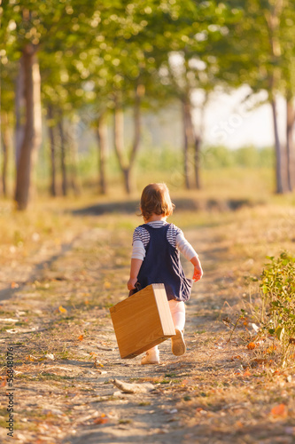 Sweet little girl playing with suitcase on the country road