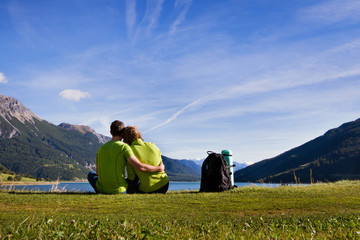 young couple of backpackers near the lake in mountains
