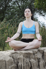 Woman sitting in lotus position on a sand cliff
