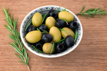 Olives with rosemary in a ceramic bowl