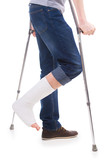 Man standing with crutches with bandage on broken leg