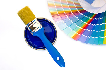 Can of blue paint with a brush and blue color swatches