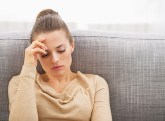 Stressed young woman sitting on sofa