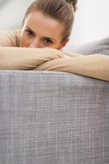 Stressed young woman sitting on couch
