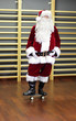 Santa Claus standing on skateboard in fitness studio