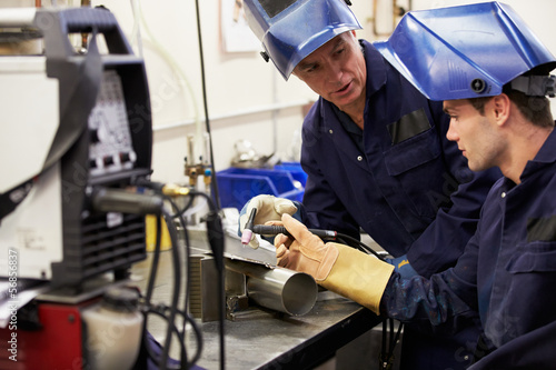Engineer Teaching Apprentice To Use TIG Welding Machine