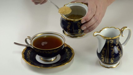 Adding brown sugar to cup of tea