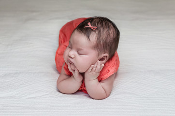Beautiful newborn baby sleeping on her elbows and hands