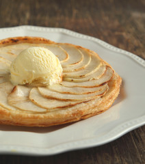 Apple tart with vanilla ice cream on wooden background. Selectiv